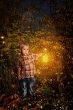 Kleines Kind, das im Nachtwald steht Stockfoto