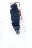 Kleines Kind, das im Schnee sledding ist Stockbilder