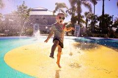 Kleines Kind, das im Wasser am Spritzen-Park am Sommer-Tag spielt stockbild