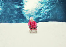 Kleines Kind, das im Winter rodelt Stockfotografie