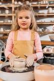 kleines Kind, das keramischen Topf mit Lehm auf Töpferscheibe herstellt lizenzfreie stockbilder