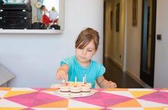 Kleines Kind, das Kerzen auf Parteikuchen setzt Lizenzfreies Stockbild