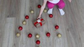 Kleines Kind, das mit neu-jährigen Spielwaren mit mehrfarbigen Bällen, Weihnachtsbällen und Kind, Geschenk spielt stock video