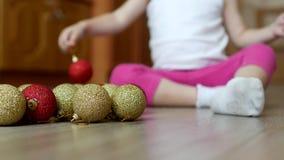 Kleines Kind, das mit neu-jährigen Spielwaren mit mehrfarbigen Bällen, Weihnachtsbällen und Kind spielt stock video