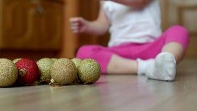Kleines Kind, das mit neu-jährigen Spielwaren mit mehrfarbigen Bällen, Weihnachtsbällen und Kind spielt stock video footage