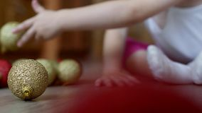 Kleines Kind, das mit neu-jährigen Spielwaren mit mehrfarbigen Bällen, Weihnachtsbällen und Kind spielt stock footage