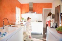 Kleines Kind, das Tablette nahe bei Mutter in der Küche betrachtet Stockfotos