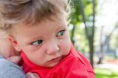 Kleines Kind, das zu Händen von seiner Mutter zurück schaut schreit Stockfoto