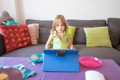 Kleines Kind, das zu Hause digitale Tablette im Sommer aufpasst Lizenzfreies Stockbild