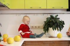 Kleines Kind in der Küche sitzt auf einer Tabelle Stockbild