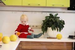 Kleines Kind in der Küche sitzt auf einer Tabelle Lizenzfreies Stockbild