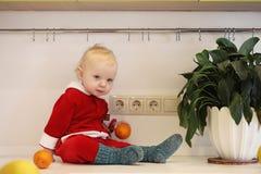 Kleines Kind in der Küche sitzt auf einer Tabelle Lizenzfreies Stockfoto