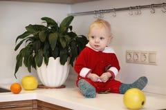 Kleines Kind in der Küche sitzt auf einer Tabelle Lizenzfreie Stockbilder