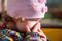 Kleines Kind in der Straße schließt sein Gesicht mit der Palme seiner Hand Stockbild