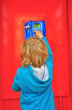 Kleines Kind in der Telefonzelle Stockbild