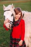 Kleines Kind des jungen Mädchens, das ein weißes Pony an seinem Kopf und an Lächeln umarmt lizenzfreies stockfoto