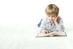 Kleines Kind des Lesebuches, das sich auf Fußboden hinlegt Lizenzfreie Stockbilder