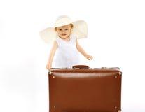 Kleines Kind in einem Strohhut und mit Koffer Stockfotos