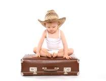 Kleines Kind in einem Strohsommerhut, der auf dem Koffer sitzt Lizenzfreie Stockbilder