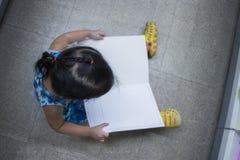 Kleines Kind erforscht und ein Buch in der Draufsicht des Buchladens lesend stockfoto