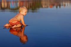 Kleines Kind hat einen Spaß auf schwarzem Sandsonnenuntergang-Seestrand stockbilder