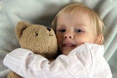 Kleines Kind im Bett mit Teddybären lizenzfreie stockfotografie