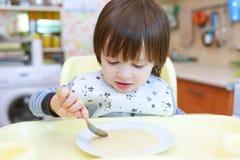 Kleines Kind isst Weizenbrei mit Kürbis Lizenzfreies Stockfoto