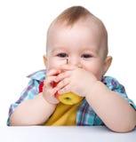 Kleines Kind ist beißender roter Apfel und Lächeln Lizenzfreie Stockfotografie