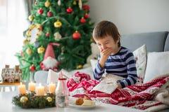 Kleines Kind, Junge, seine Nase durchbrennend und herein niesen, Lügenkranker lizenzfreie stockfotografie