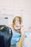 Kleines Kind lernt, Eltern zu helfen, seinen Kopf zu halten Stockfoto