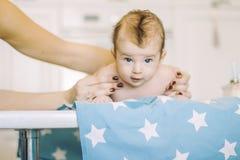Kleines Kind lernt, Eltern zu helfen, seinen Kopf zu halten Stockbilder