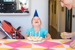 Kleines Kind mit dem Geburtstagskuchen, der nahe bei Frau horselaughing ist Stockfotos