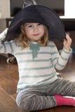 Kleines Kind mit dem Hexenhut, der auf Boden sitzt Stockfotos