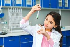 Kleines Kind mit dem Lernen der Klasse im Schullaborbetriebssprössling stockfotografie