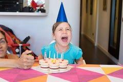 Kleines Kind mit dem Parteikuchenschreien verärgert Stockfotos