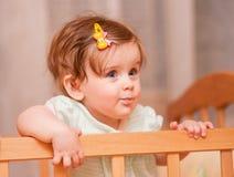 Kleines Kind mit einer Haarnadel, die in der Krippe steht Lizenzfreies Stockbild