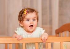 Kleines Kind mit einer Haarnadel, die in der Krippe steht Stockfoto