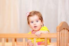 Kleines Kind mit einer Haarnadel, die in der Krippe steht lizenzfreie stockbilder