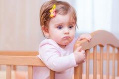 Kleines Kind mit einer Haarnadel, die in der Krippe steht stockbild