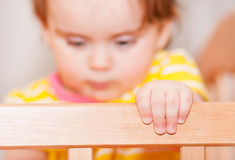 Kleines Kind mit einer Haarnadel, die in der Krippe steht Unscharfer Hintergrund lizenzfreies stockbild