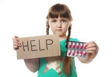 Kleines Kind mit Pillen und Wort Hilfe geschrieben auf Pappe Gefahr der Medikamentintoxikation stockfotografie