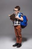 Kleines Kind mit Schultasche und Buch im Studio Stockfotografie