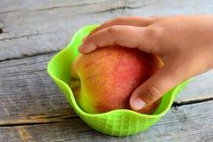 Kleines Kind nimmt einen frischen Pfirsich in seiner Hand Süße juisy Pfirsiche auf einem Weinleseholztisch Natürliche Nahrung Stockfoto