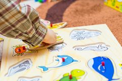 Kleines Kind setzt das einfache Puzzlespiel auf den Boden Stockfotos