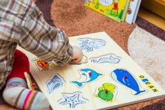 Kleines Kind setzt das einfache Puzzlespiel auf den Boden Lizenzfreies Stockbild
