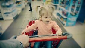 Kleines Kind sitzt in einer Laufkatze, Gegähne, seine Elternteilrollen entlang Regalen mit Waren im Speicher stock video footage