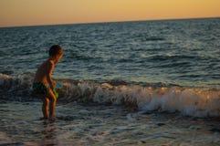 Kleines Kind spielt mit Wasser welle Strand stockfotos