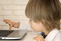 Kleines Kind und Laptop Stockfotos