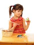 Kleines Kind, welches die Ostereier malt Lizenzfreie Stockfotografie