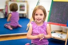 Kleines Kind zeichnet mit Farbkreide auf dem Kreidebrett Lizenzfreies Stockfoto